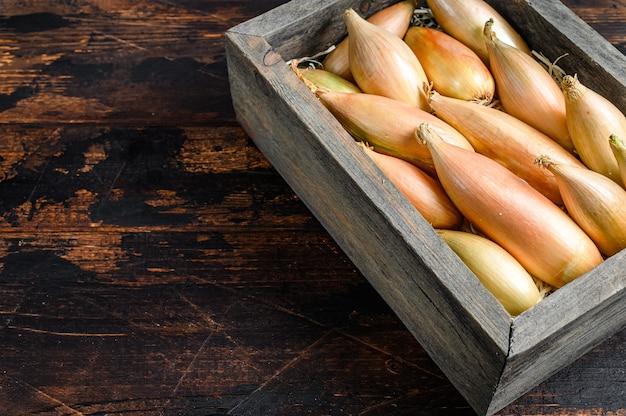Cebolas de chalota frescas cruas bulbos em uma caixa de madeira do mercado. fundo de madeira escuro. vista do topo. copie o espaço.