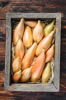 Cebolas de chalota frescas cruas bulbos em uma caixa de madeira do mercado. fundo de madeira escuro. vista do topo.
