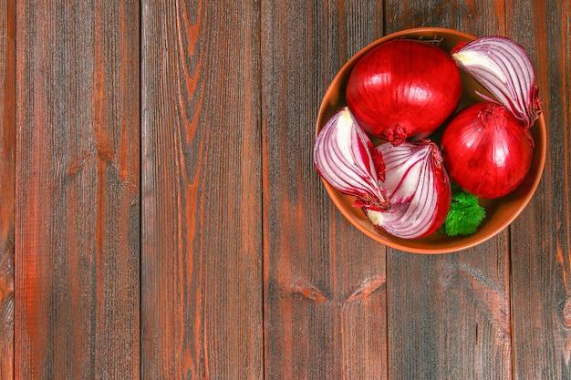 Cebolas vermelhas frescas e fatias desbastadas em uma tabela de madeira. vista do topo.