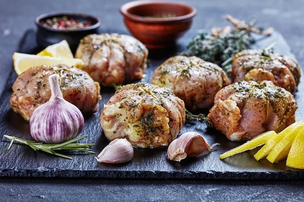 Cédula de coelho cru preparada para ser cozida em um prato de ardósia preta com ervas e temperos, vista horizontal de cima, close-up