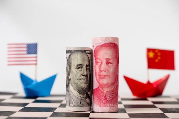 Cédula do dólar e do yuan de américa no tabuleiro de xadrez com os eua e as bandeiras de china.