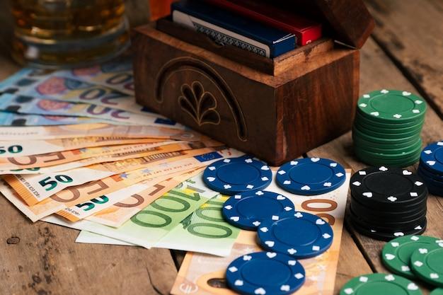 Cédulas ao lado de fichas de pôquer e copo de uísque