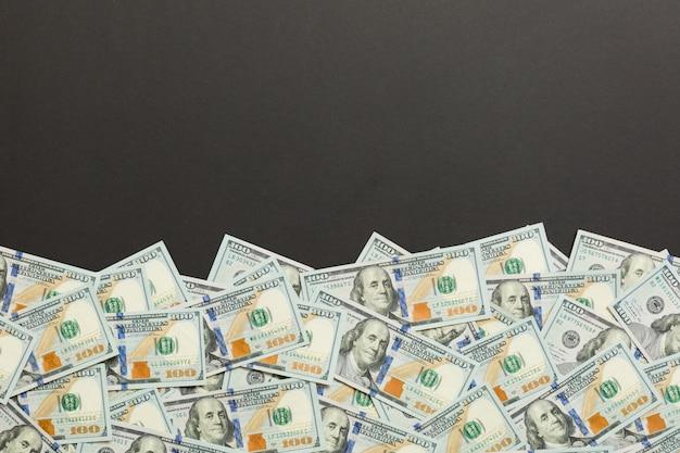Cédulas da vista superior na mesa colorida com copyspace na parte superior. notas de cem dólares com pilha de dinheiro no meio. vista superior do negócio