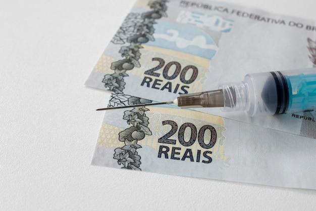 Cédulas de dinheiro brasileiro e seringa com agulha