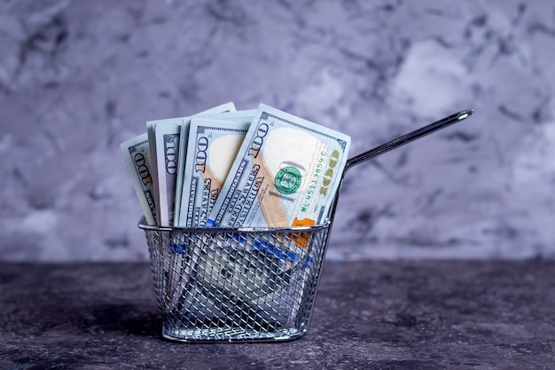 Cédulas de dinheiro em uma peneira funda para abrir um fast food para pequenas empresas em um fundo cinza