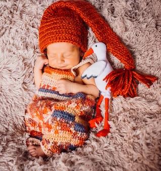 Cegonha de brinquedo abraça bebê pequeno em chapéu vermelho