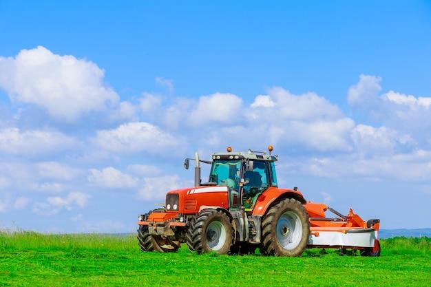 Ceifa. um grande trator vermelho com um cortador de grama corta a grama no campo em um dia ensolarado.