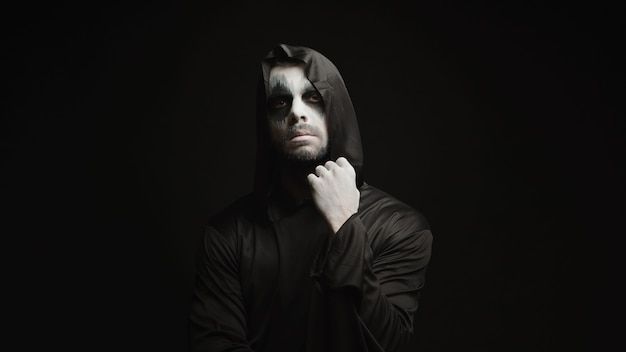 Ceifador assustador pensativo sobre fundo preto. demônio de halloween.