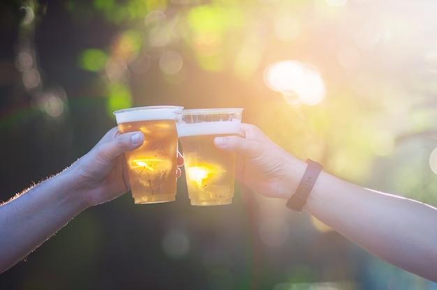 Celebração cerveja cheers conceito - close-up mãos segurando copos de cerveja