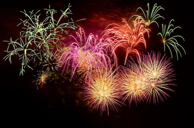 Celebração colorida dos fogos-de-artifício e o fundo do céu noturno.