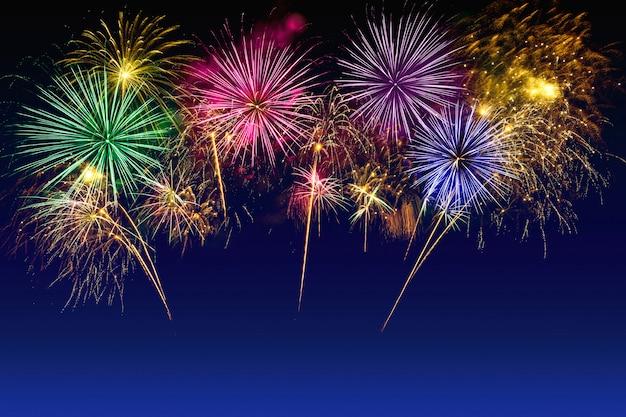 Celebração colorida dos fogos-de-artifício no céu crepuscular.