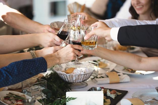 Celebração, comer e feriados conceito - mãos tilintar de copos de vinho