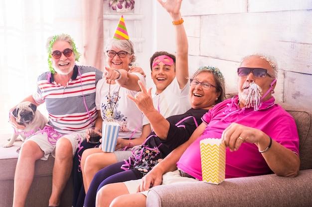 Celebração da festa de carnaval como aniversário ou véspera de ano novo para famílias com várias gerações, de opld a adolescente. cão pug também, todos se divertem juntos em casa