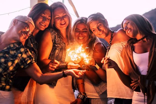 Celebração da festa de véspera de ano novo - amigos celebrando juntos com conceito de amor e amizade - grupo de mulheres sorri e se divertem à noite com fogos de artifício e risos