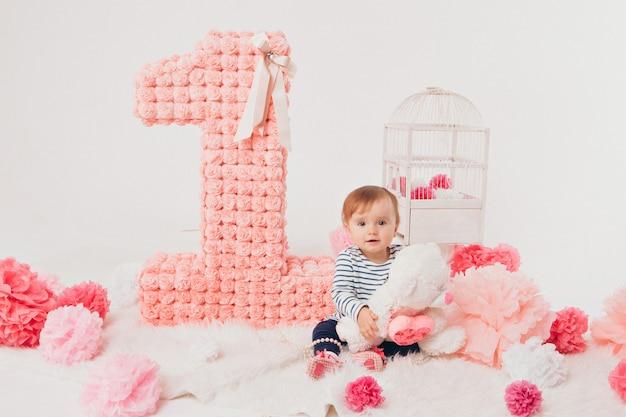 Celebração de aniversário: menina sentada no chão entre os números 1
