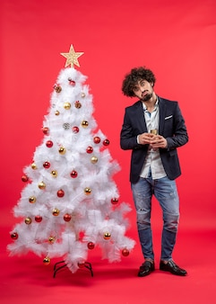 Celebração de ano novo com jovem confuso segurando uma taça de vinho perto da árvore de natal branca decorada