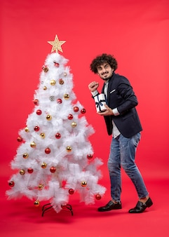 Celebração de ano novo com jovem mostrando seu presente feliz perto da árvore de natal branca decorada em imagens vermelhas