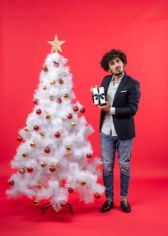 Celebração de ano novo com jovem mostrando seu presente perto da árvore de natal branca decorada em imagens vermelhas
