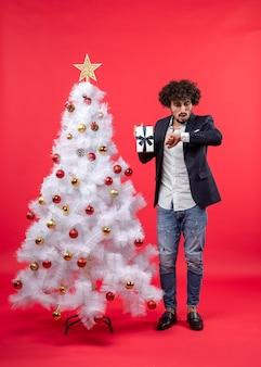 Celebração de ano novo com o jovem mostrando seu presente e verificando as horas perto da árvore de natal branca decorada