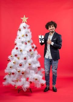 Celebração de ano novo com o jovem mostrando seu presente fazendo um gesto de ok perto da árvore de natal branca decorada em vermelho