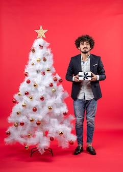 Celebração de ano novo com um jovem sério segurando um presente perto da árvore de natal branca decorada em filmagens vermelhas