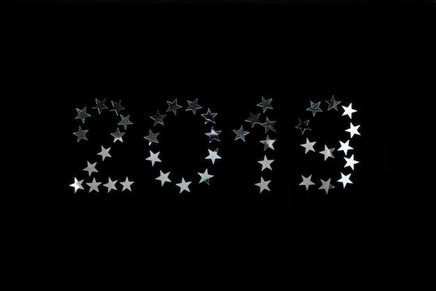 Celebração de ano novo de 2019. estrela de prata polvilha confetes em fundo preto