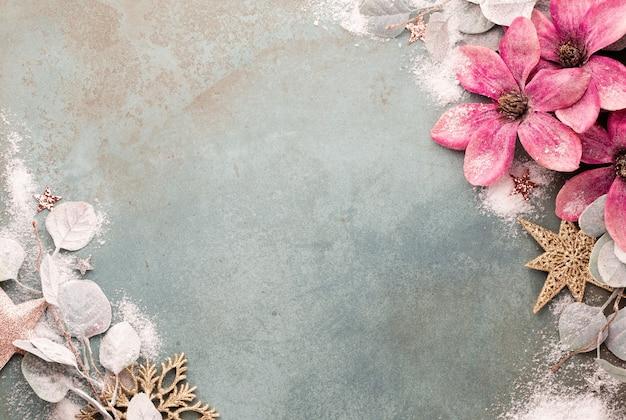 Celebração de ano novo e fundo de natal com vista superior de flores cor de rosa, neve, estrelas e decorações de natal.