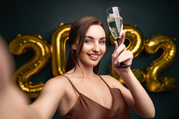 Celebração de ano novo linda mulher morena fazendo selfie na frente de balões dourados backg preto ...
