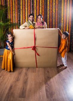 Celebração de diwali ou rakshabandhan - jovem família indiana de quatro pessoas celebrando o festival deepavali ou bhai dooj com doce laddoo, lâmpada a óleo ou diya e caixas de presente, comendo comida ou tomando selfie