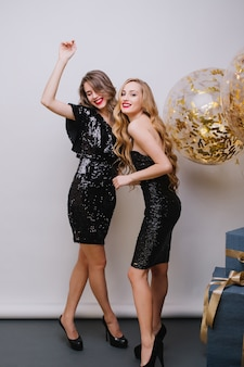 Celebração de festa feliz e brilhante de duas incríveis mulheres jovens e atraentes em vestidos pretos de luxo se divertindo na parede branca. grandes balões cheios de ouropéis dourados, presentes, expressando positividade.
