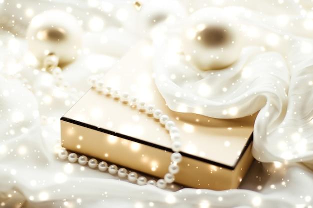 Celebração de inverno e decoração de natal de conceito de véspera de ano novo com neve brilhante em background de seda ...