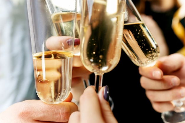 Celebração de mãos segurando taças de champanhe e vinho fazendo um brinde