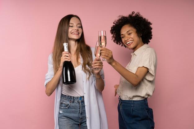 Celebração de mulheres com taças de champanhe e garrafa