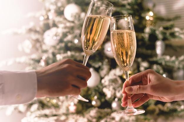 Celebração de natal. casal segurando copos de vinho espumante