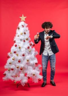 Celebração de natal com um jovem barbudo com vinho, verificando o tempo e em pé perto da árvore de natal no vermelho