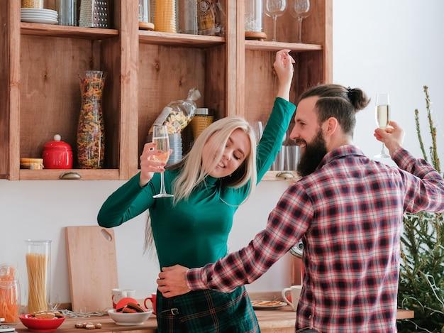 Celebração de natal em casa. casal feliz dançando na cozinha com taças de champanhe.