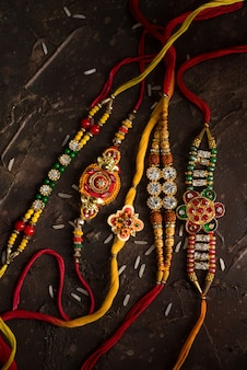 Celebração de raksha bandhan com um elegante rakhi e arroz espalhado. pulseira tradicional indiana, símbolo de amor entre irmãos e irmãs.