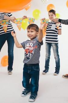 Celebração, diversão, passar tempo, família na festa. adultos e crianças em um fundo branco entre as bolas coloridas comemoram seu aniversário