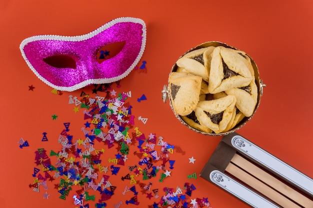 Celebração do carnaval judaico de purim com biscoitos hamantaschen, noisemaker e máscara