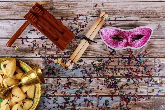 Celebração do carnaval judaico de purim em biscoitos hamantaschen, noisemaker e máscara com pergaminho vista superior de cima.