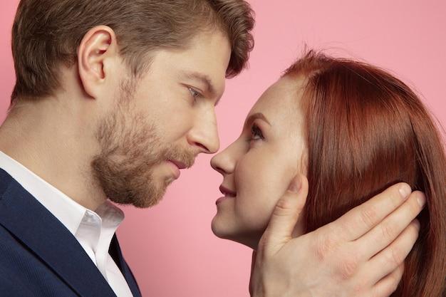 Celebração do dia dos namorados, close-up do casal caucasiano beijando e sorrindo no fundo do estúdio coral. conceito de emoções humanas, expressão facial, amor, relações, férias românticas.