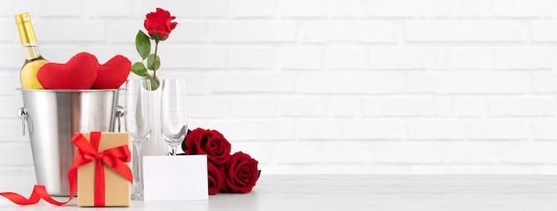 Celebração do dia dos namorados com vinho, presente e buquê de rosa para saudação de feriado.