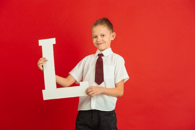 Celebração do dia dos namorados. feliz, bonito garoto caucasiano segurando a carta no fundo vermelho do estúdio.
