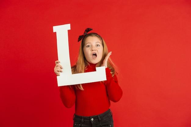 Celebração do dia dos namorados, feliz, linda garota caucasiana segurando a carta no fundo vermelho do estúdio.