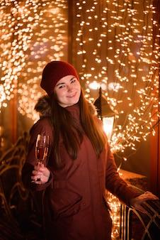 Celebração do feriado de natal. menina bebendo champanhe no feriado brilhante fundo dourado.