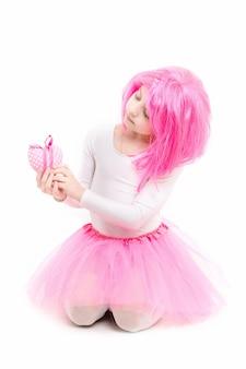 Celebração do feriado e dia das mães. natal e aniversário. infância e felicidade. criança na peruca isolada no fundo branco. menina pequena com coração dia dos namorados em saia rosa.