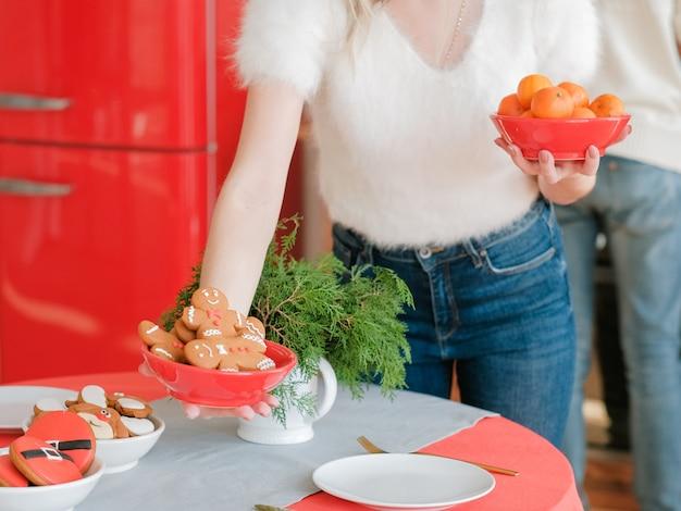 Celebração do natal. senhora arrumando mesa festiva com tangerinas e biscoitos de gengibre