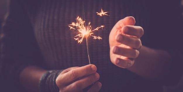 Celebração e evento festa conceito close up de um par de mãos pegando e usando fogos de artifício luz de fogos de artifício e se divertindo