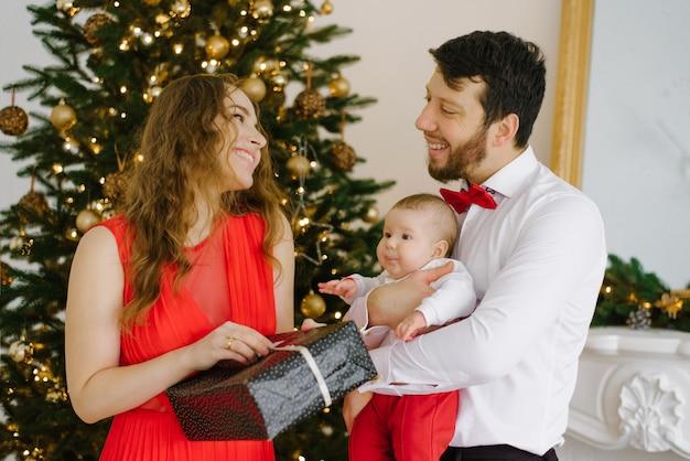Celebração familiar de natal e ano novo por uma jovem família com uma criança pequena perto da árvore de natal. eles se dão presentes