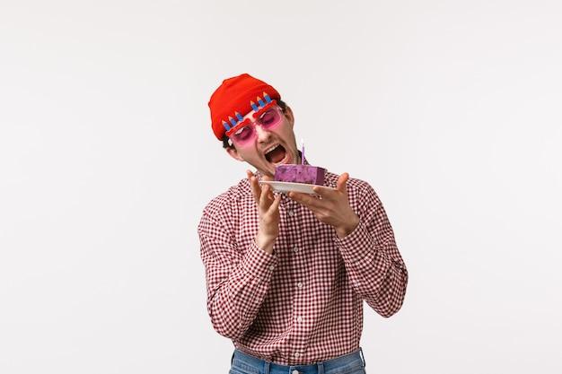 Celebração, feriados e conceito de estilo de vida. cara de hipster adulto engraçado e fofo comemorando aniversário, usar óculos escuros e morder o delicioso bolo de aniversário, comer sobremesa saborosa, carrinho